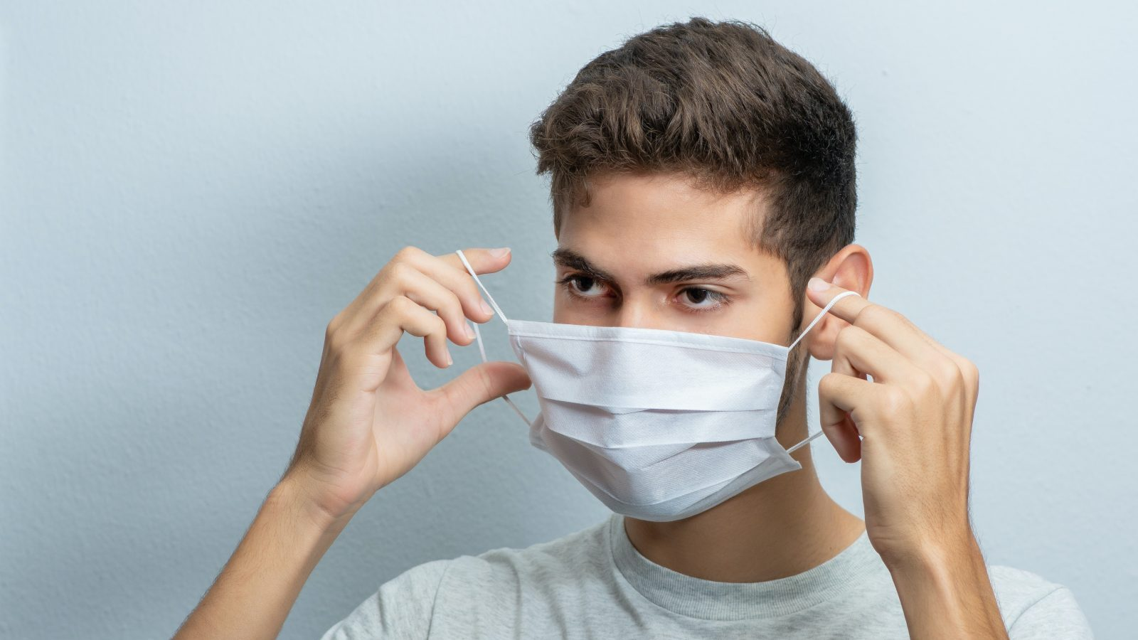 man in gray crew neck t-shirt covering his face with white textile