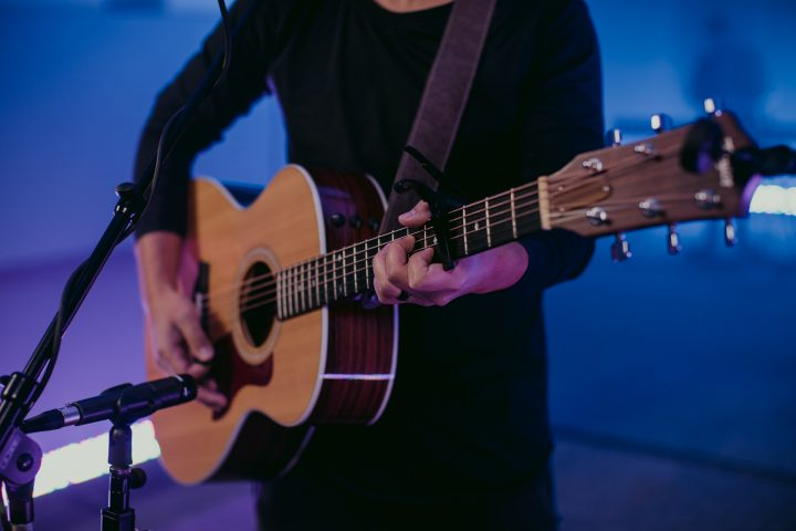 man in black long sleeve shirt playing brown acoustic guitar